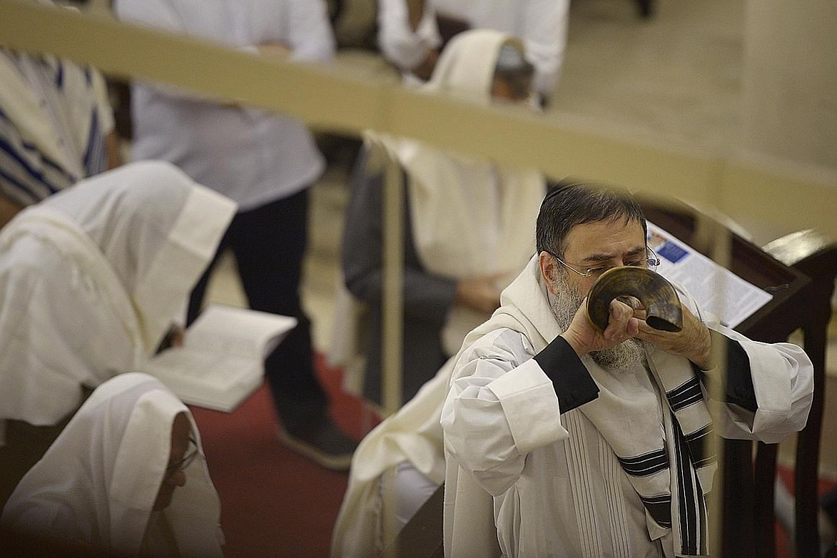 Rabbi Abergel (above) blows the Shofar - a traditional instrument made from the horn of a ram - to mark the end of the fasting period.