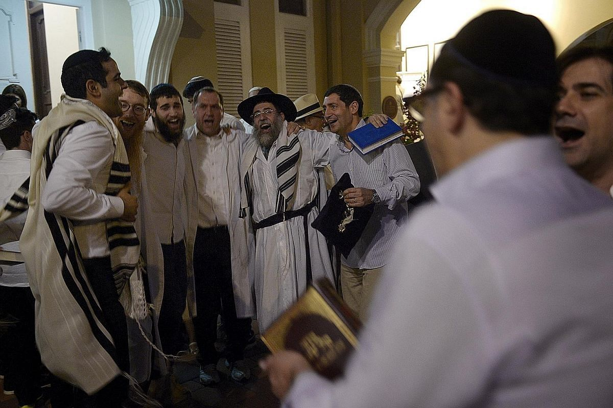 Rabbi Mordechai Abergel (centre, wearing a hat) and other men from the Jewish community dance and sing to celebrate the end of the fasting period during Yom Kippur – the holiest festival in the Jewish calendar – at the Maghain Aboth Synagogue in Waterloo