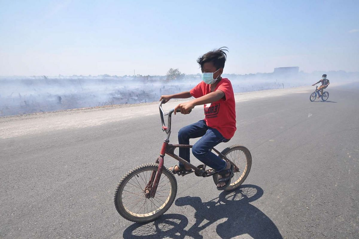 Children ride their bicycles while wearing face masks to protect them from pollution caused by haze in the Banjarbaru district of South Kalimantan province on Oct 8, 2015. Indonesia agreed on Oct 8 to accept international help to combat forest and ag