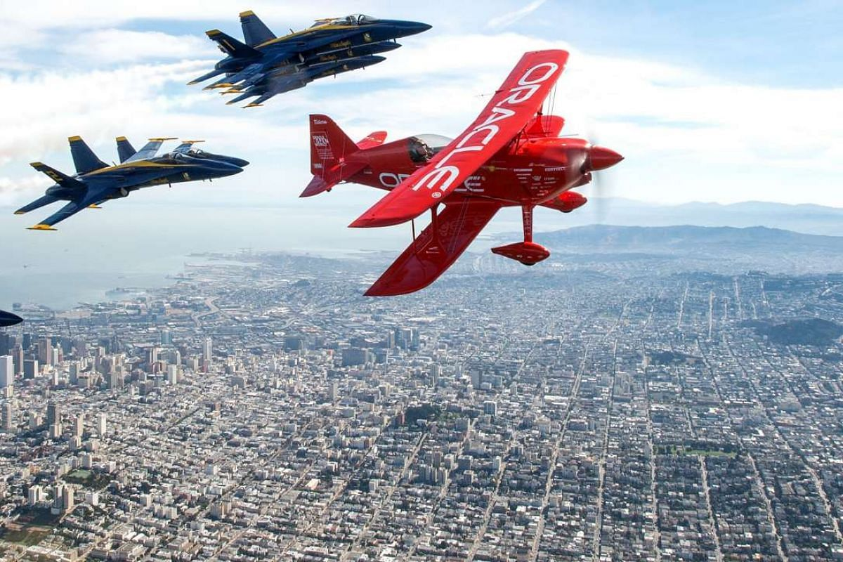 Team Oracle stunt pilot Sean Tucker (R) flies ahead of the U.S. Navy Blue Angels (L) as part of a practice run for Fleet Week over the bay in San Francisco, California on Oct 8, 2015. Fleet Week started on Oct 5 and goes till Oct 12 and will include