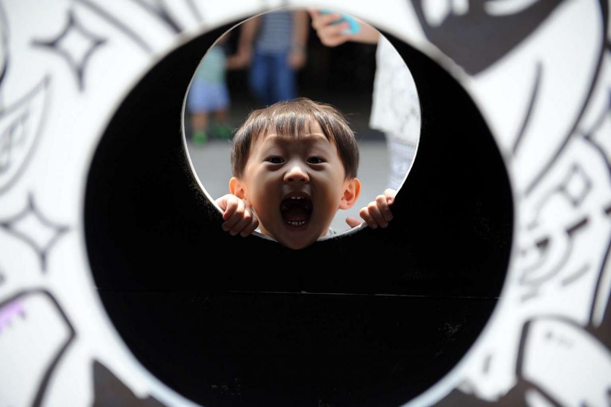 A young boy popping his head through the window of Doodle City - one of the exhibit displayed outside Esplanade Theatres in celebration of Octoburst! A Children's Festival. Many kids here are celebrating Children's Day on Oct 9, 2015, in the outdoors