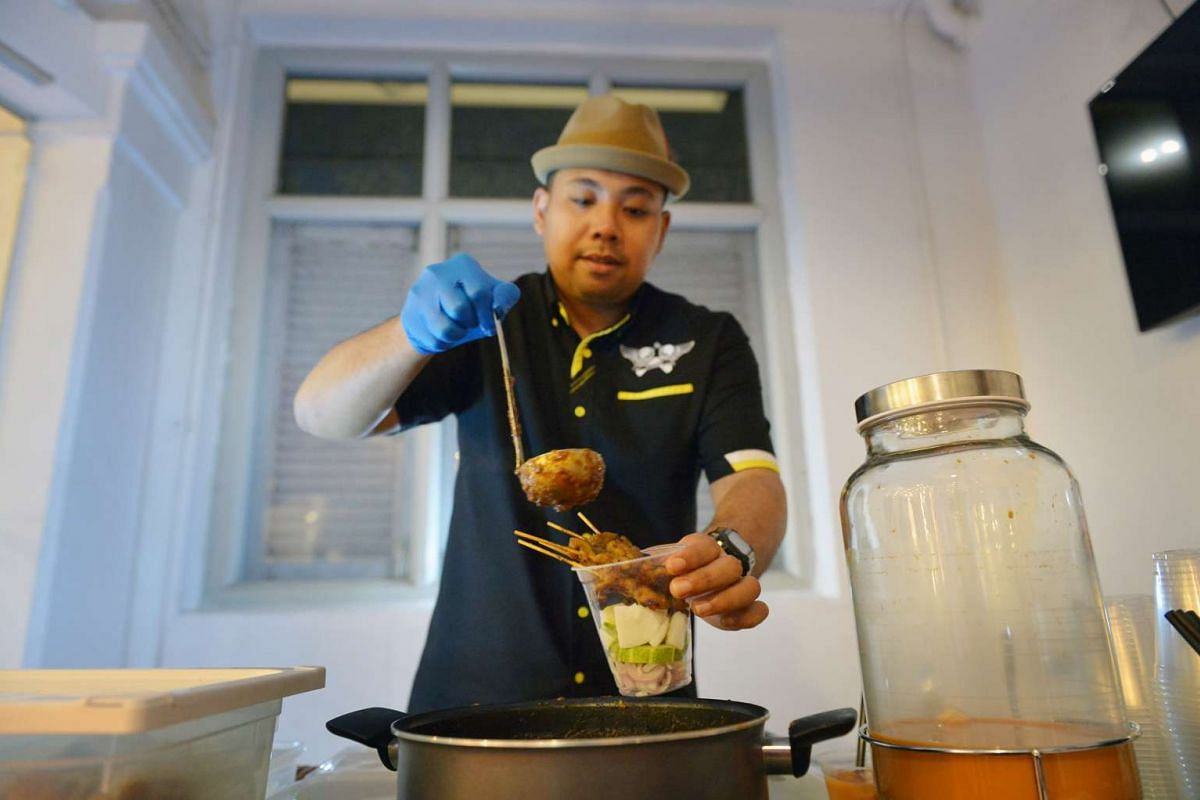 Mr Mohamed Dino Shafique serving up satay in a cup.