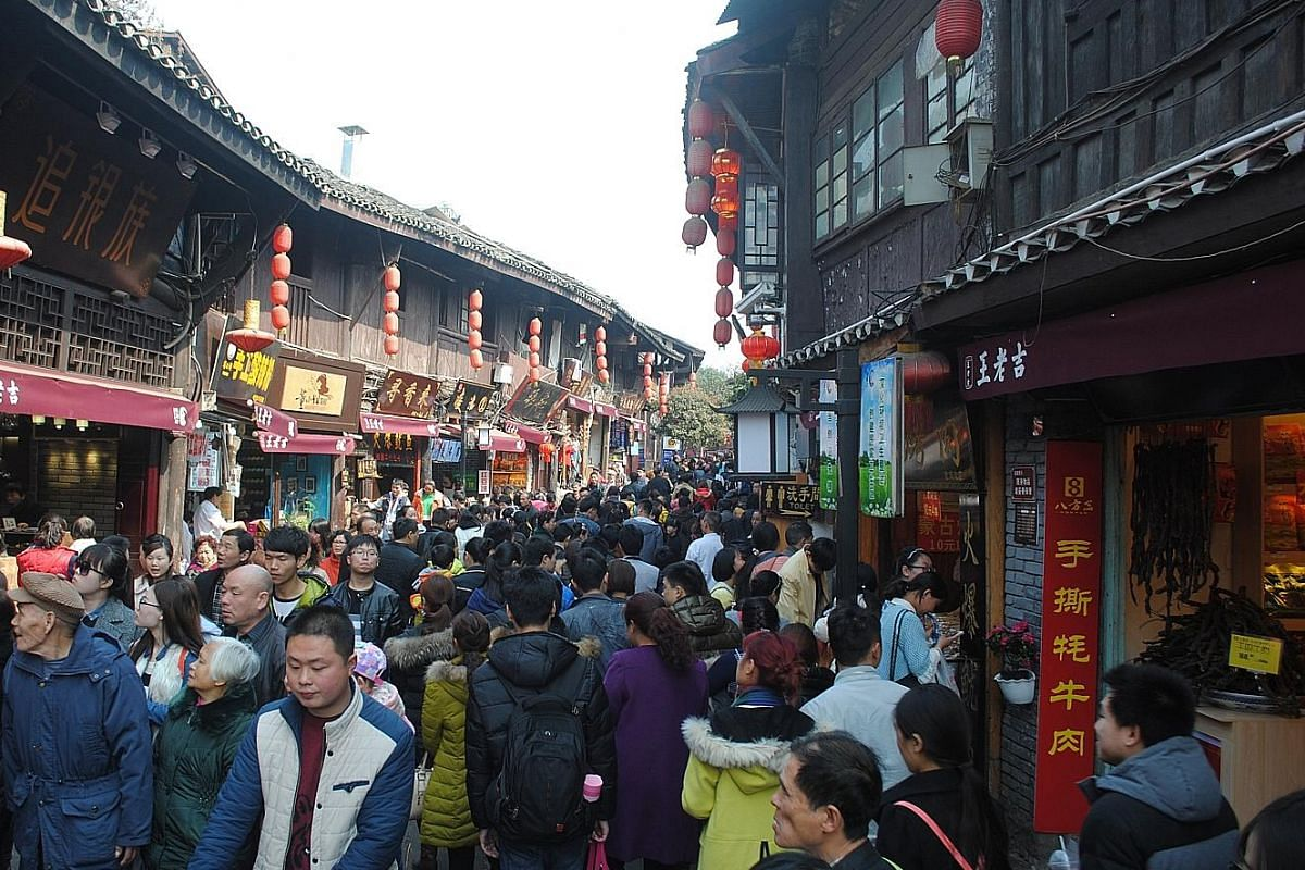 Crowds throng the narrow streets of Ciqikou (above), which are lined with souvenir and food shops.