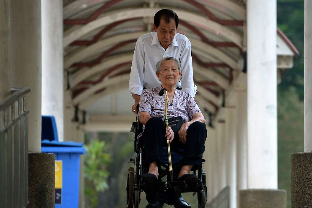 Retiree Lim Toaw Luan takes care of his mother, Madam Foo Eng Lan, who moves with difficulty after a fall last year.
