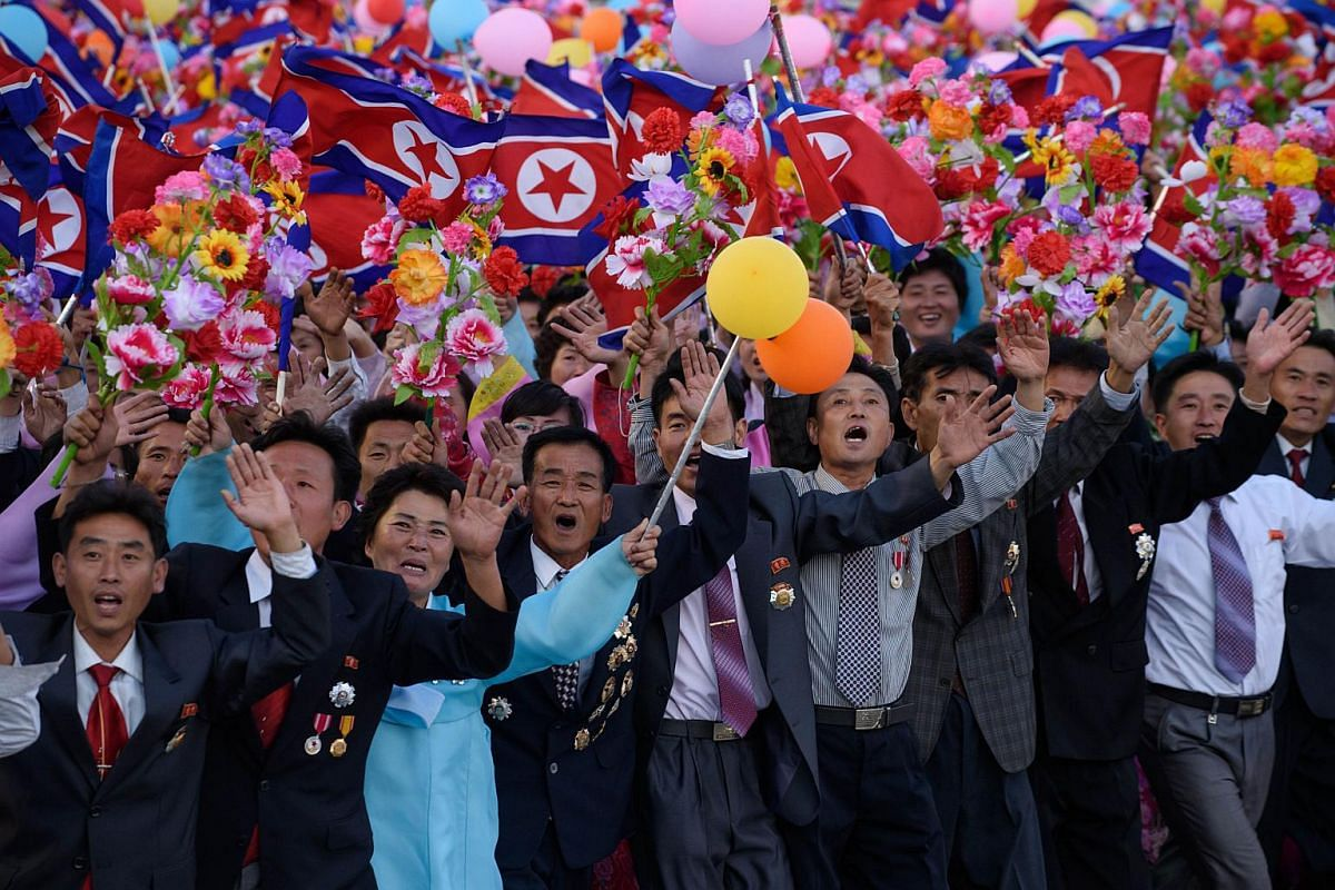 North Koreans cheering during a mass military parade at Kim Il Sung Square in Pyongyang on Oct 10, 2015.