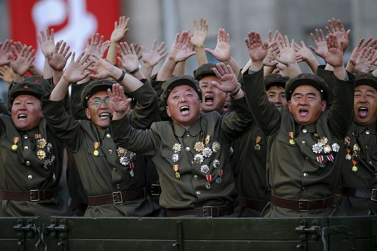 Veteran soldiers cheering as North Korean leader Kim Jong Un is driven past them at a parade celebrating the 70th anniversary of the founding of the ruling Workers' Party of Korea in Pyongyang on Oct 10, 2015.