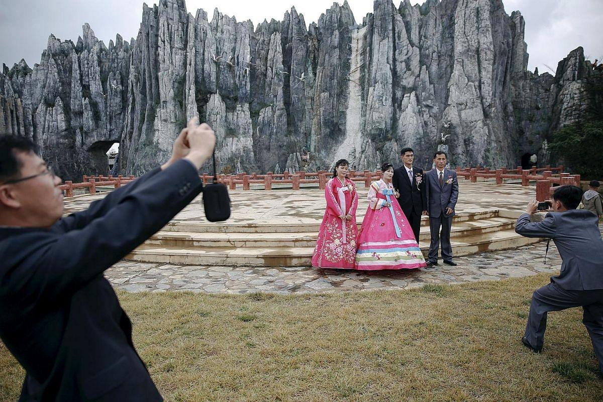 Ms O Yang Ran and her husband Kim Chol Nam (centre) accompanied by friends during a photo shoot at Pyongyang Folk Park on Oct 11, 2015.
