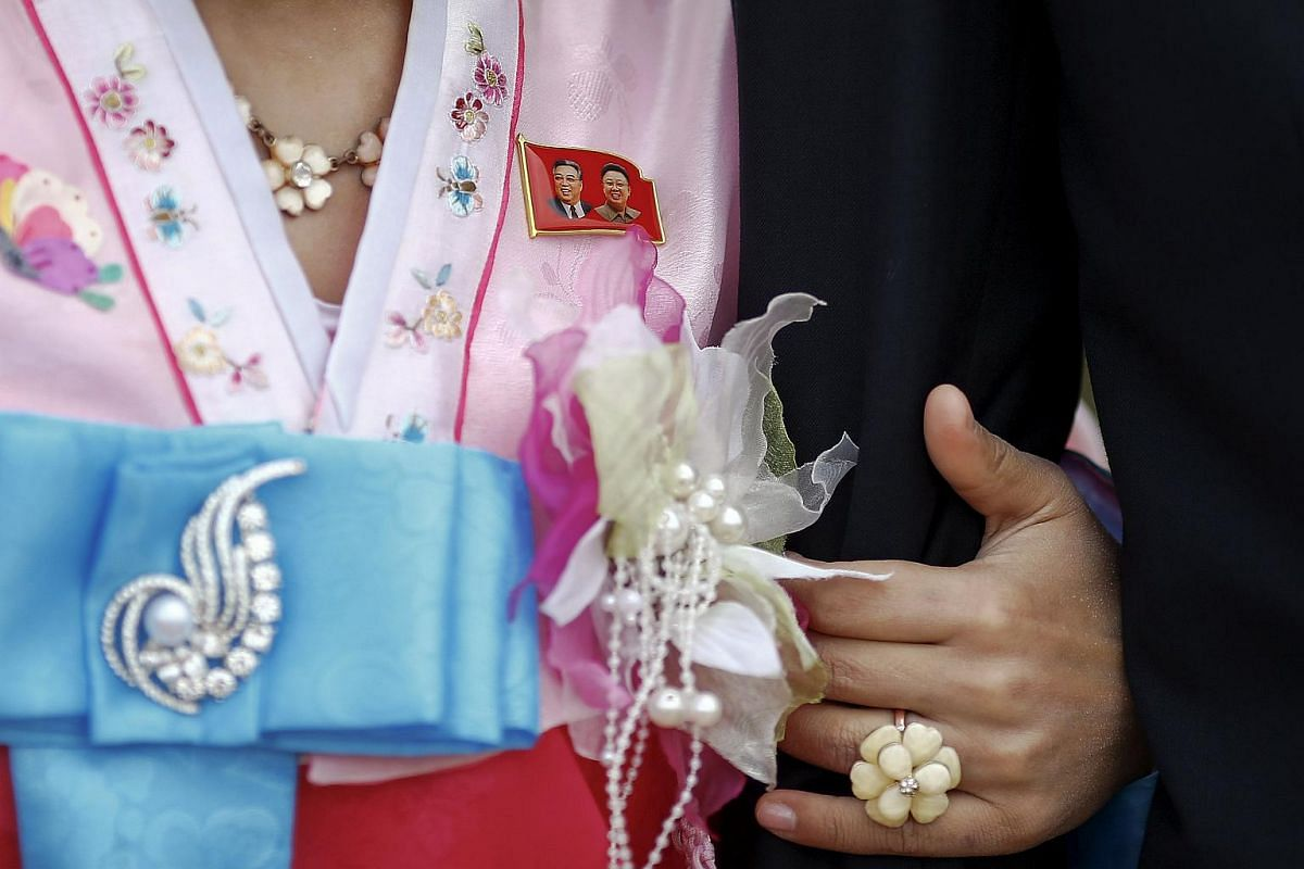 A pin showing North Korea's founder Kim Il Sung (left) and former leader Kim Jong Il decorates the wedding dress of a North Korean bride on Oct 11, 2015.