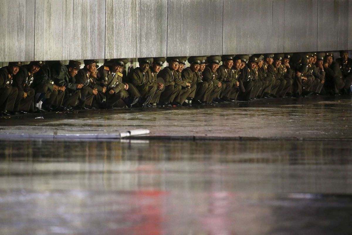 North Korean officers shielding themselves from the rain after a parade celebrating the 70th anniversary of the founding of the ruling Workers' Party of Korea in Pyongyang on Oct 10, 2015.