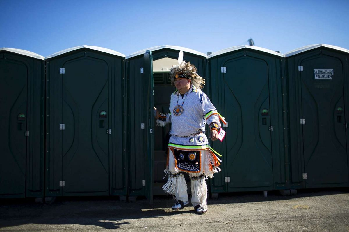 """A reveller exiting a mobile toilet during a """"pow-wow"""" celebrating the Indigenous Peoples' Day Festival in Randalls Island, New York, on Oct 11, 2015. The festival is held as a counter-celebration to Columbus Day and to promote Native American culture"""