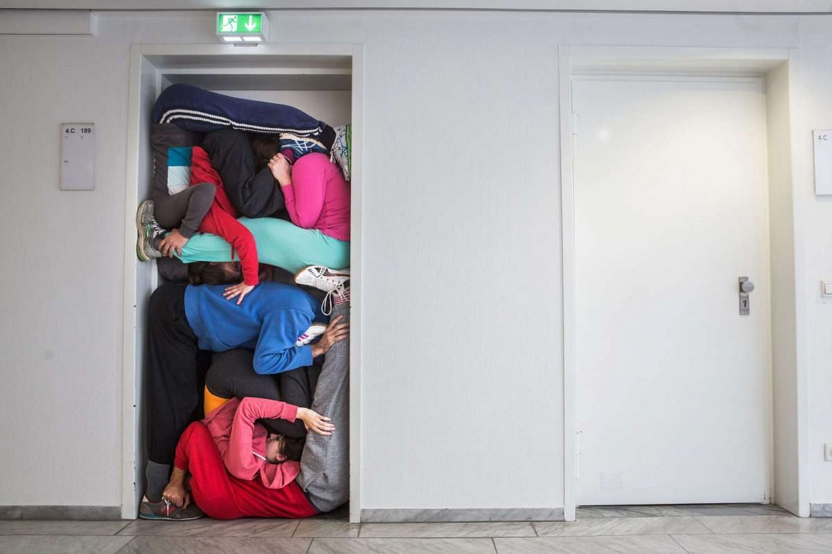 Members of a performance troupe led by Austrian choreographer Willi Dorner squeezing themselves into a doorway at the 2015 Frankfurt Book Fair, in Frankfurt am Main, Germany, on Oct 13, 2015. The performance will be part of Austria's new cultural cam
