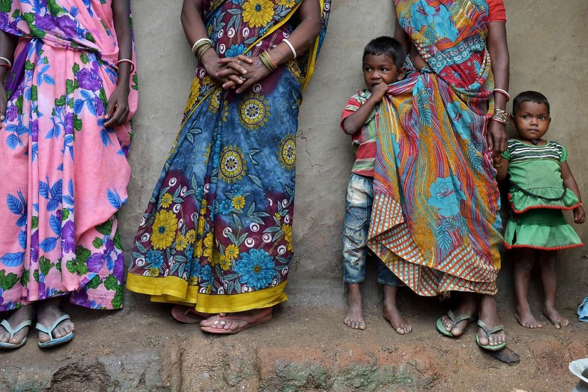 Indian tribal villagers dependent upon the mica mining industry standing near a traditional home at Koderma District in the eastern Indian state of Jharkhand. The mica adds glitter to powders, mascara and lipsticks of top global brands although a com