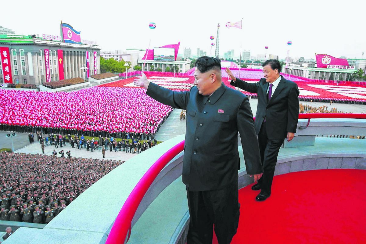 North Korean leader Kim Jong Un (front) and China's Mr Liu Yunshan waving to the crowd during a large-scale military parade at the Kim Il Sung Square in Pyongyang last Saturday to mark the 70th anniversary of the ruling Workers' Party of Korea.