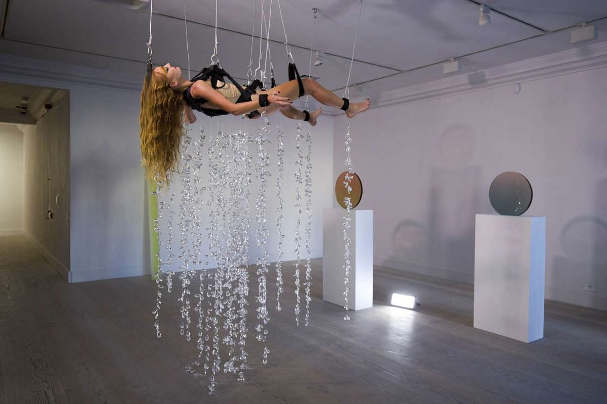 British artist Millie Brown performing Rainbow Body, a performance installation where she is surrounded by crystal prisms suspended from the ceiling at Gazelli Art House in London on Oct 14, 2015, on the sidelines of the Frieze Art Fair.