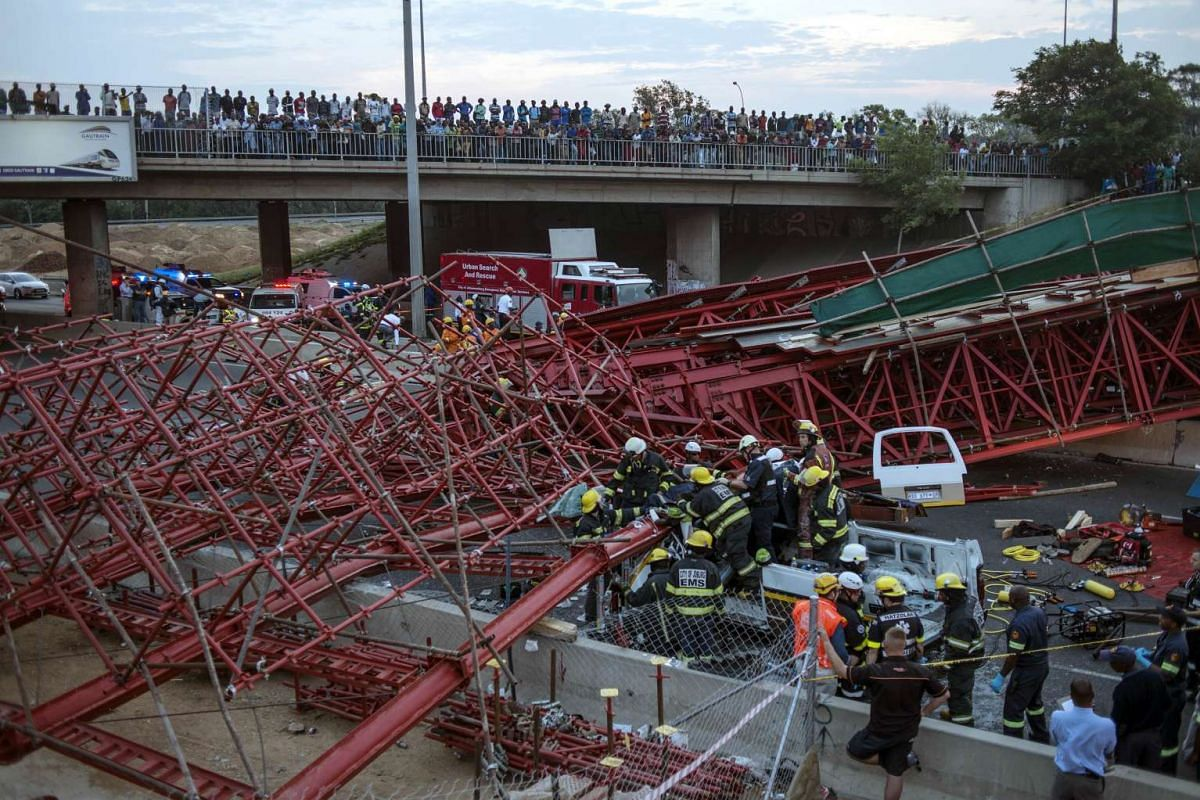 South African paramedics and first aid team working on the rubble of a collapsed pedestrian bridge where at least two people were killed, on Oct 14, 2015, in Johannesburg.