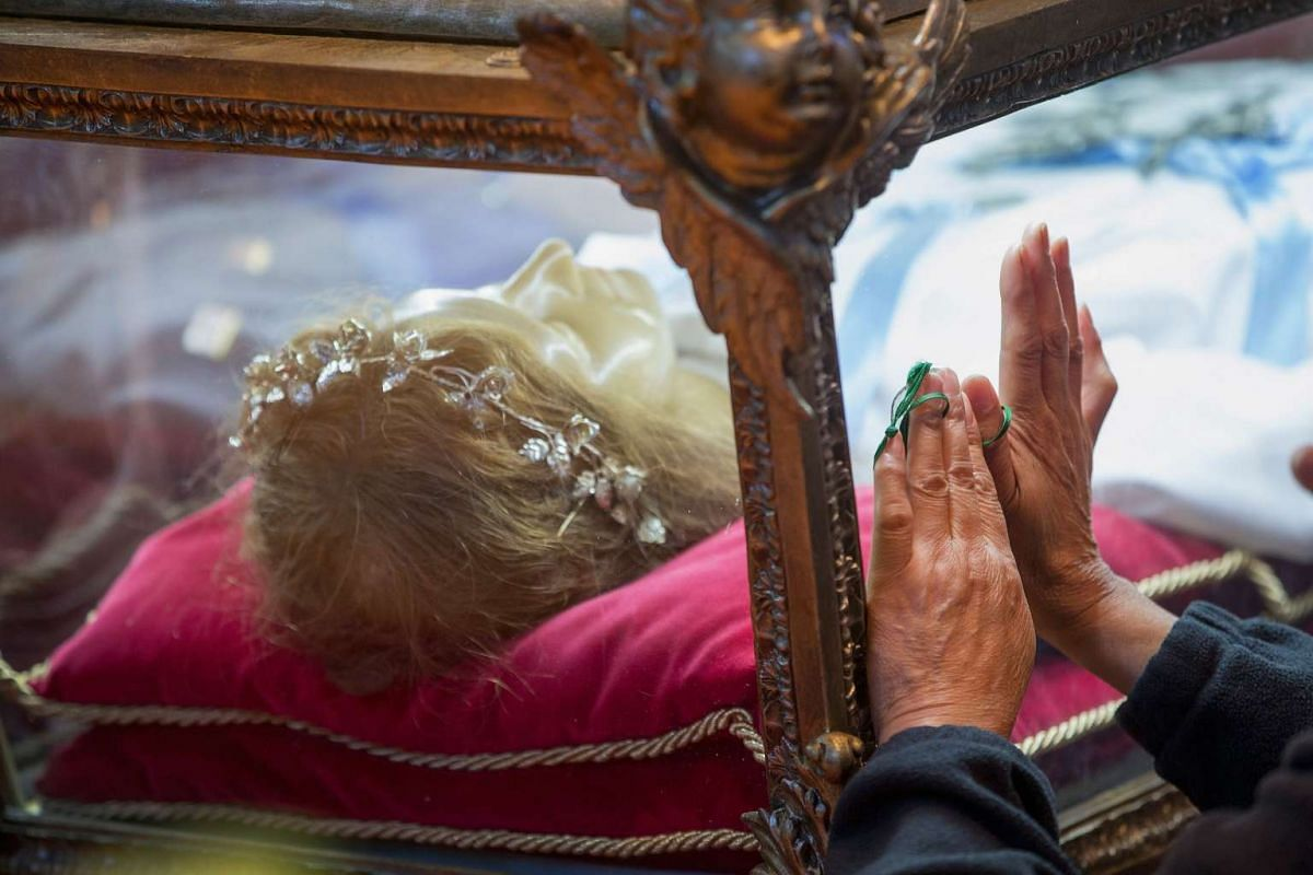 Visitors praying over the remains of Saint Maria Goretti at Saint Francis Assisi Church on Oct 14, 2015, in Orland Park, Illinois. Goretti, the youngest canonised saint in the Catholic Church, was murdered during an attempted rape by Alessandro Seren
