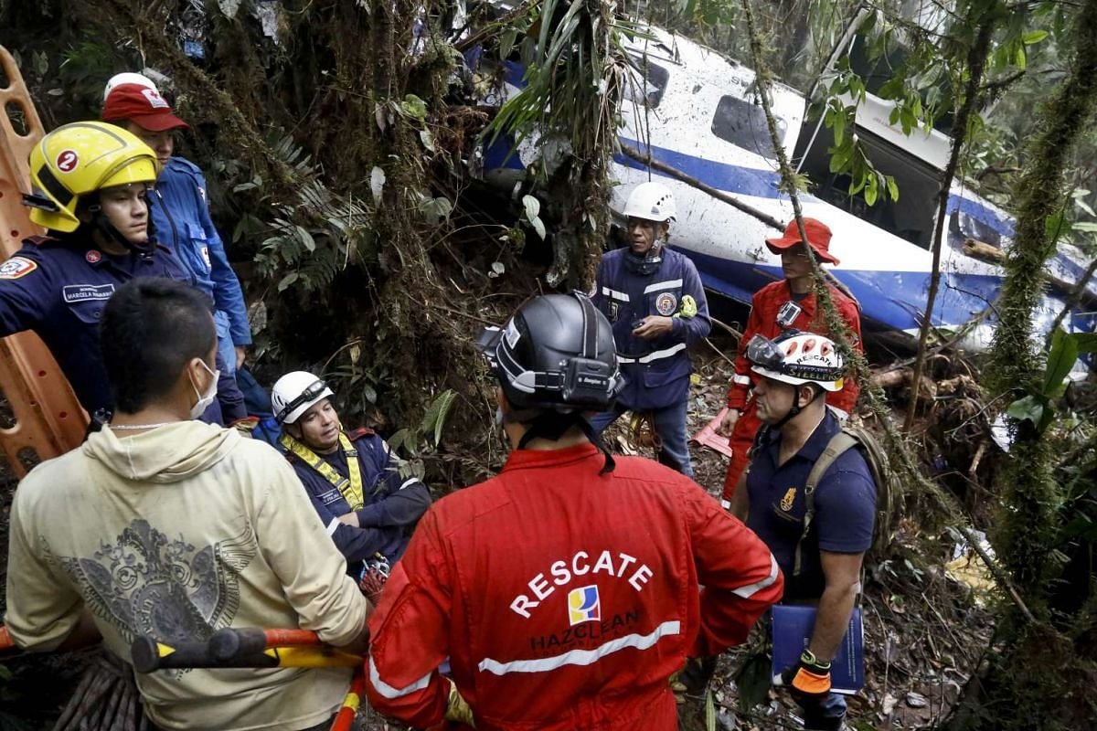 Rescuers standing next to the remains of a Brazilian aircraft that crashed in rural Yumbo, department of Valle del Cauca, Colombia, on Oct 14, 2015. The Cessna 208 aircraft with a Brazilian licence plate was reported missing while on geographical aer