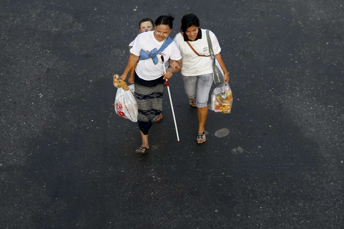 A visually impaired woman (left) carrying a child on her back as a volunteer helps her during a rally to mark International White Cane Day, in Yangon, Myanmar, on Oct 15,2015. White Cane Safety Day celebrates the achievements of blind or visually imp