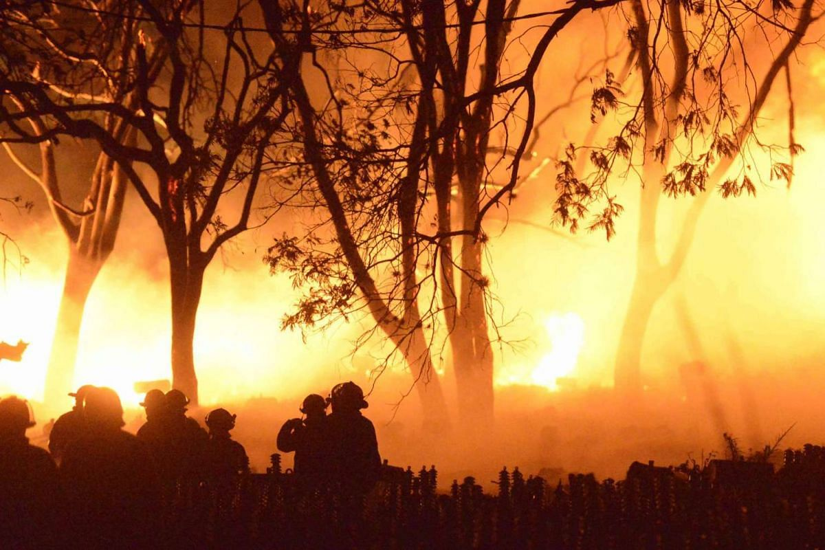 Paraguayan firefighters trying to extinguish a fire in a building in the Laurel neighborhood, of San Lorenzo, near Asuncion, Paraguay, on Oct 14, 2015.