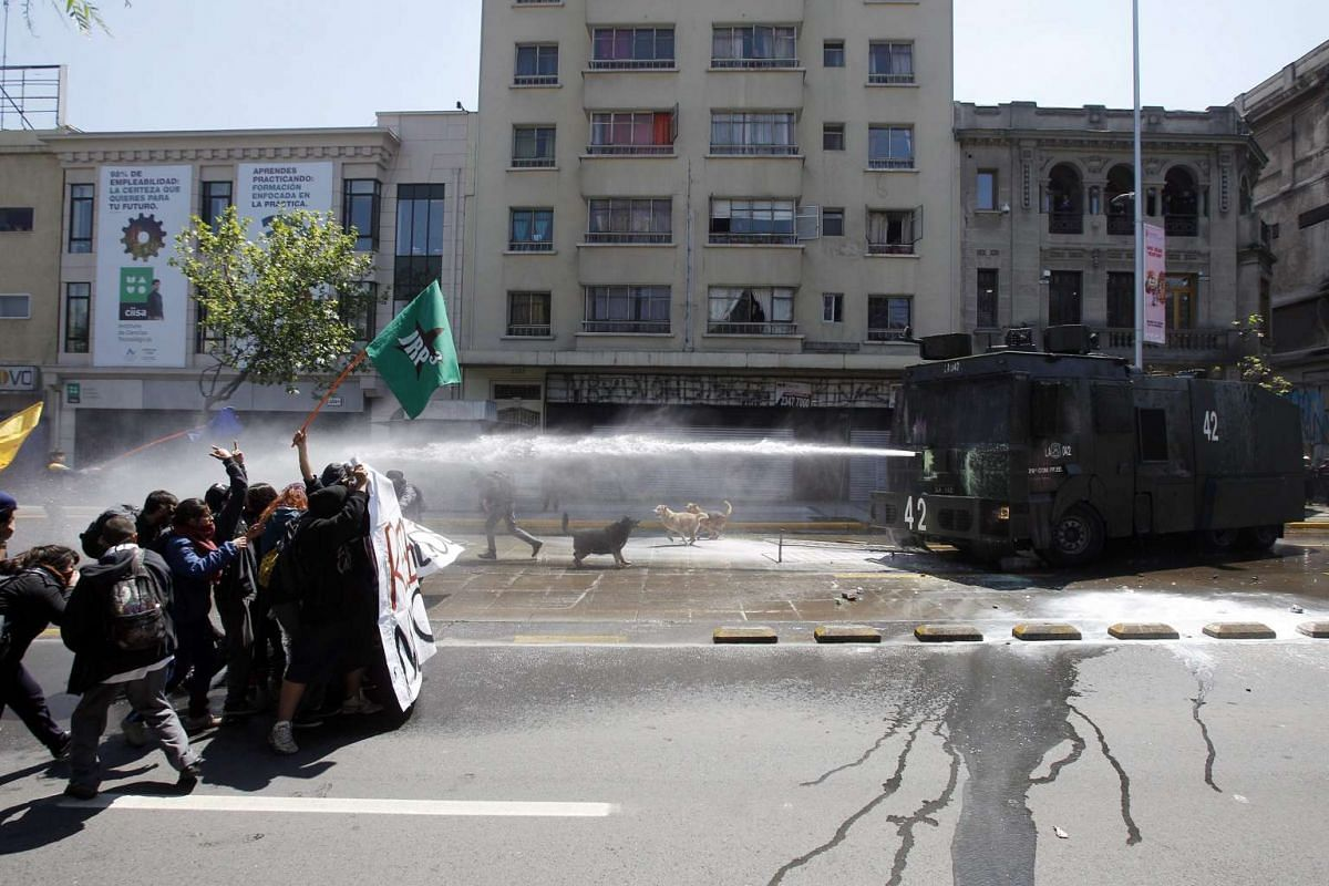 Police using a water cannon against demonstrators during a march called by the Confederation of Chilean Students (Confech) to reject the changes announced by the government to an education Bill, in Santiago, Chile, on Oct 15, 2015.