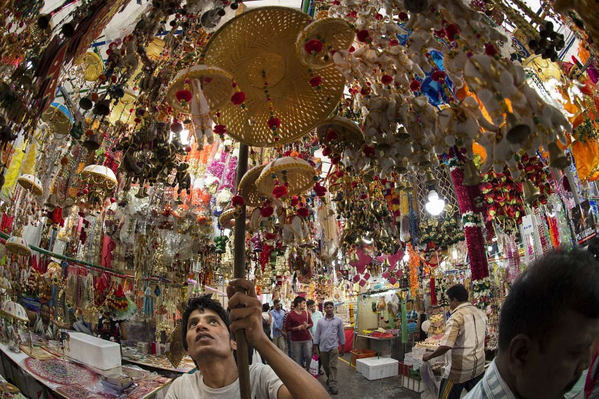 A stallholder hanging up torans, or wall hangings, for sale at the Deepavali Festival Village in Little India.