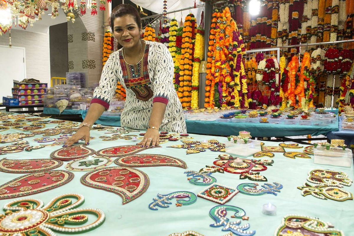 Ms Prithikha Sankar, 16, helping her father man their stall selling rangoli and other decorative items for Deepavali.
