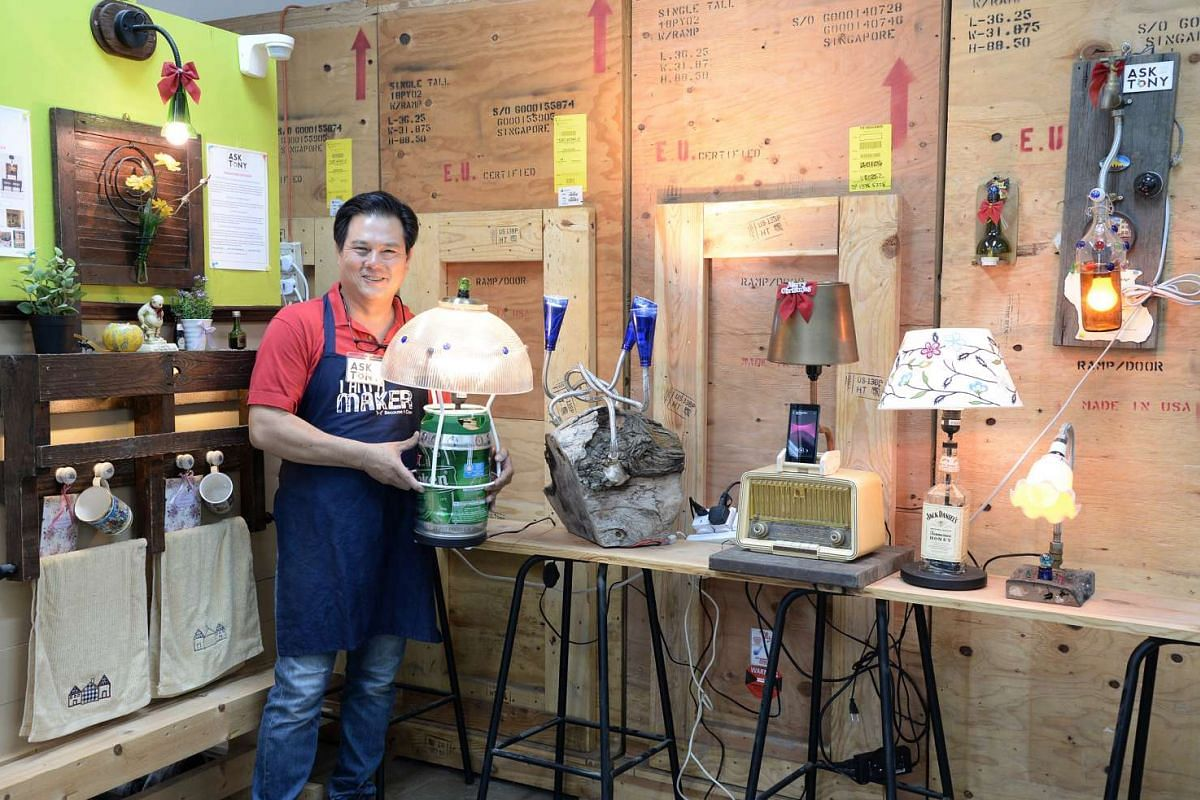 Mr Tony Goh (above) with some of his table lamps made from unwanted materials and Ms Nur Liyana Omar repairing her niece and nephew's toy trains.
