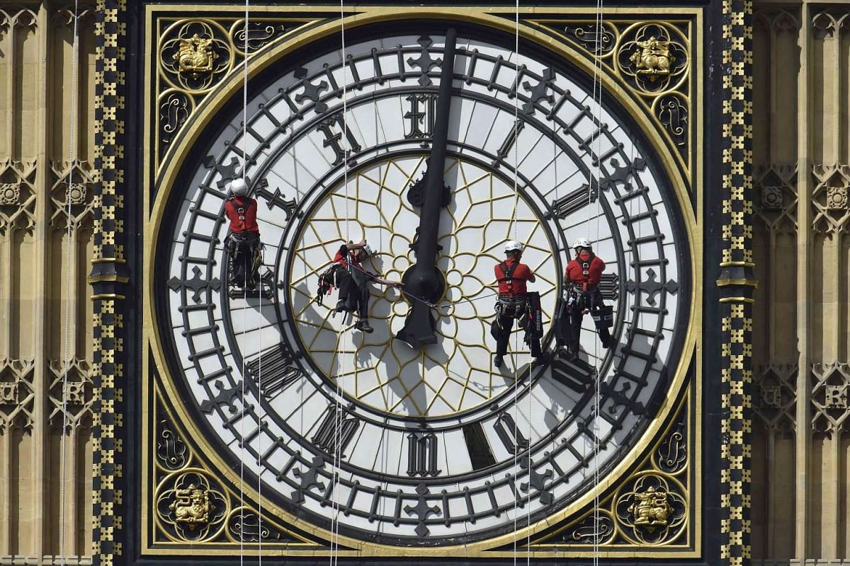 Cleaners abseil down one of the faces of Big Ben, to clean and polish the clock face, above the Houses of Parliament, in central London in this file picture taken Aug 19, 2014. London's 156-year-old Big Ben clock - which has already shown signs of it