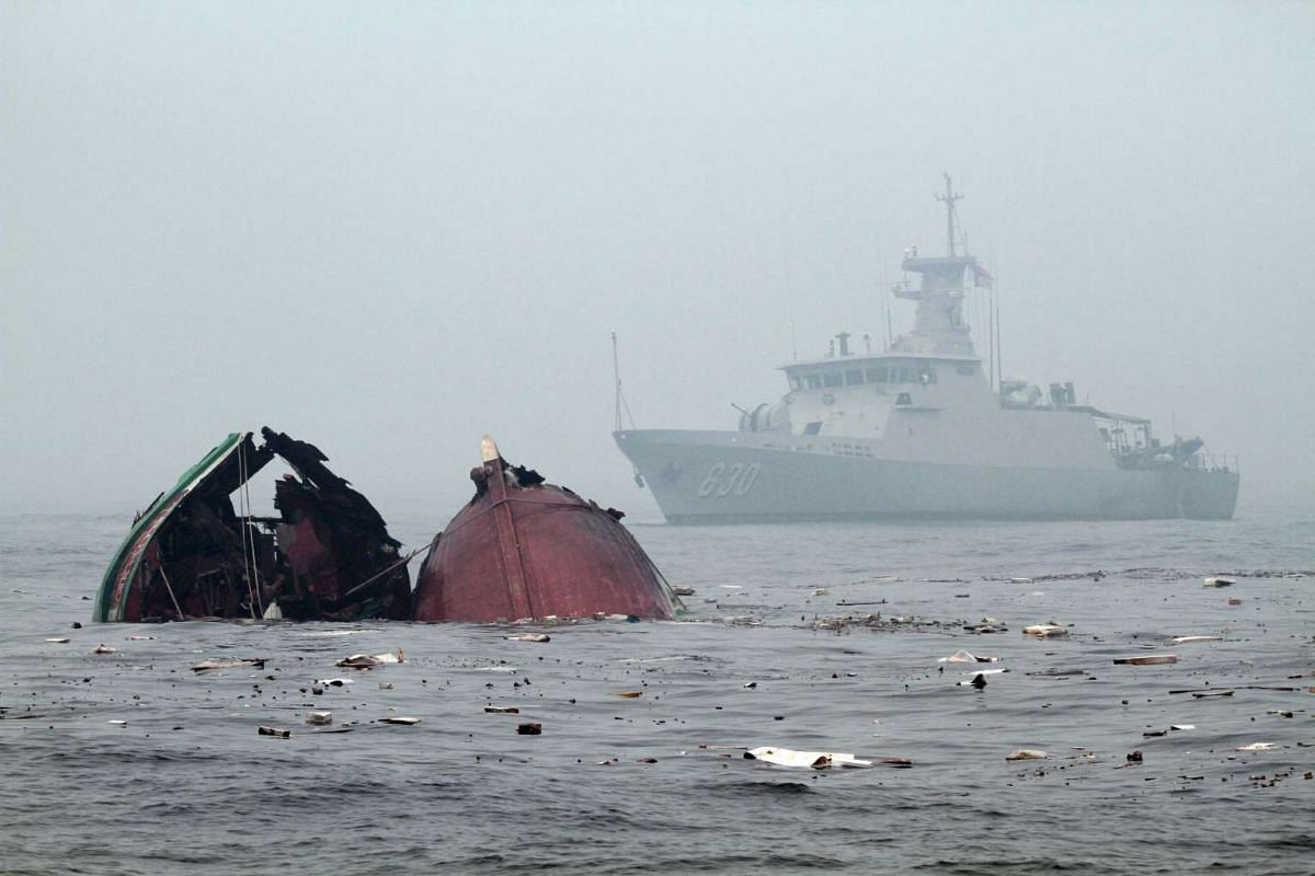 An Indonesian Navy ship patrol as a fishing vessels from Vietnam caught fishing illegally in Indonesian sea start to sink after it were blown up by the Navy, on the water of Pontianak, West Kalimantan province, Indonesia, Oct 19, 2015. According to m