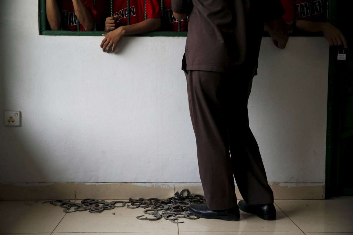 A court official stands in front of a cell as prisoners wait their for trial at Batam District Court, Indonesia Riau Islands, Oct 19, 2015.