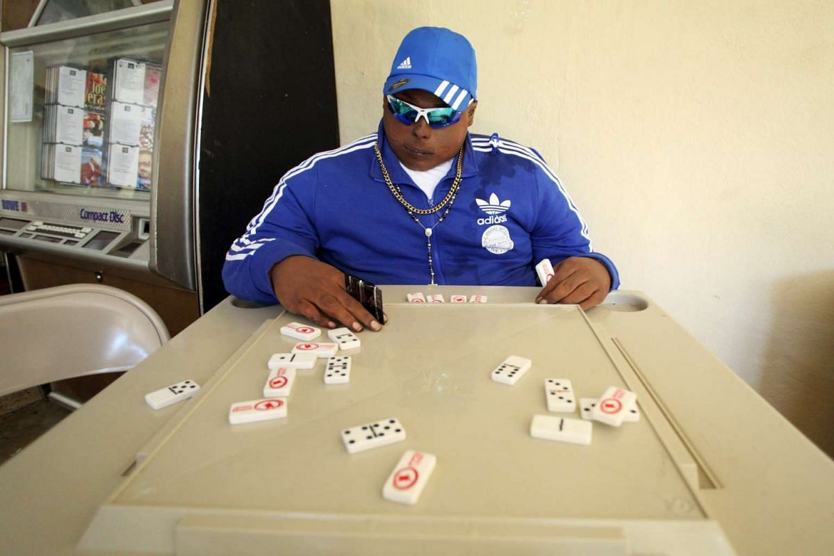 The dead body of Jomar Aguayo is seated at a table with domino tiles and with a condom placed in one of his hands in San Juan, Oct 19, 2015. Aguayo's family decided, with the help of a funeral home that specializes in embalming techniques, to have hi
