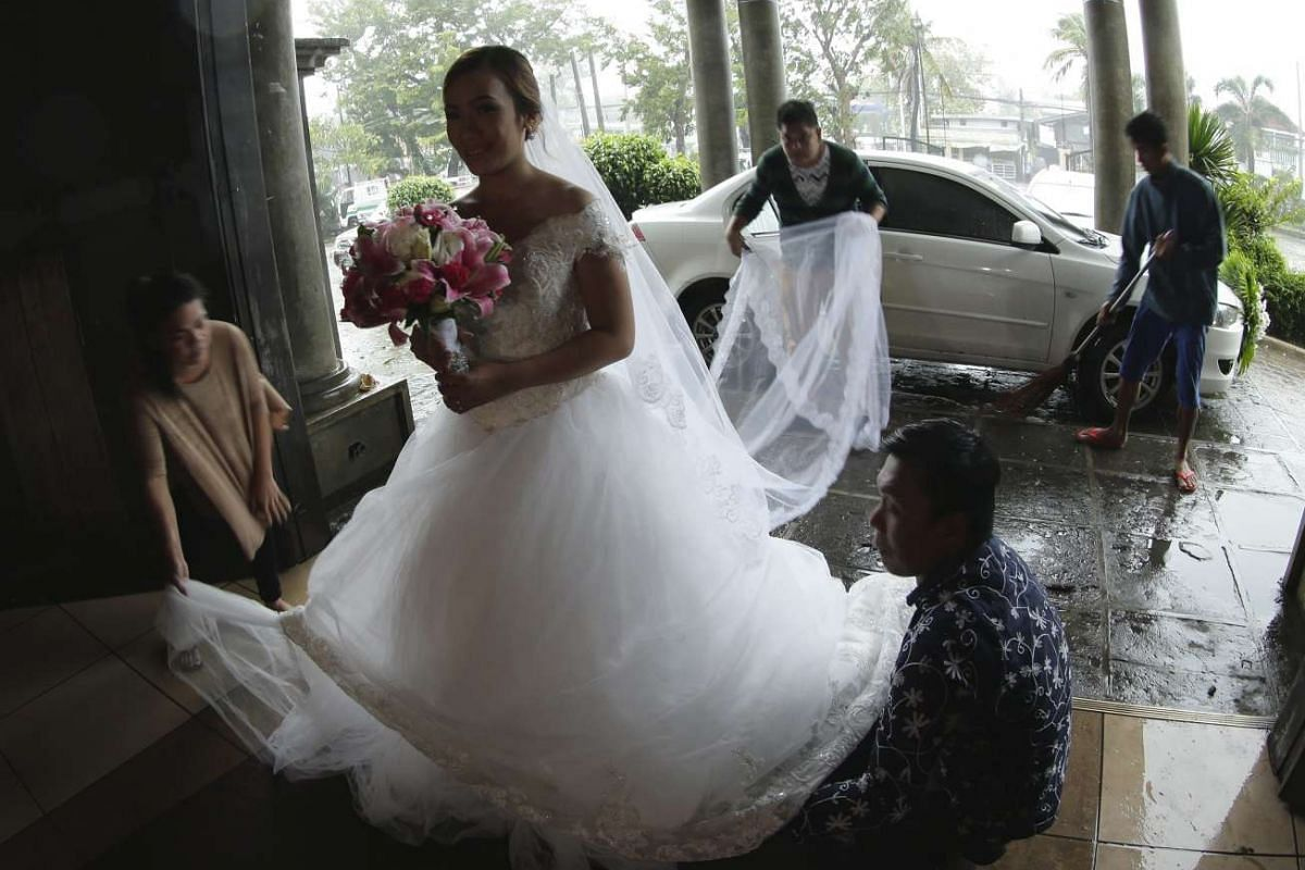 Bride Madel Ortega arrives at her wedding ceremony amidst the storm at a church in San Jose city on Oct 18.