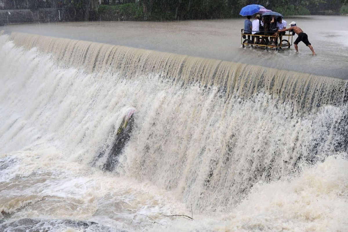 Residents crossing a swelling dam, due to rising waters brought about by Typhoon Koppu, in Las Pinas city on Oct 19.