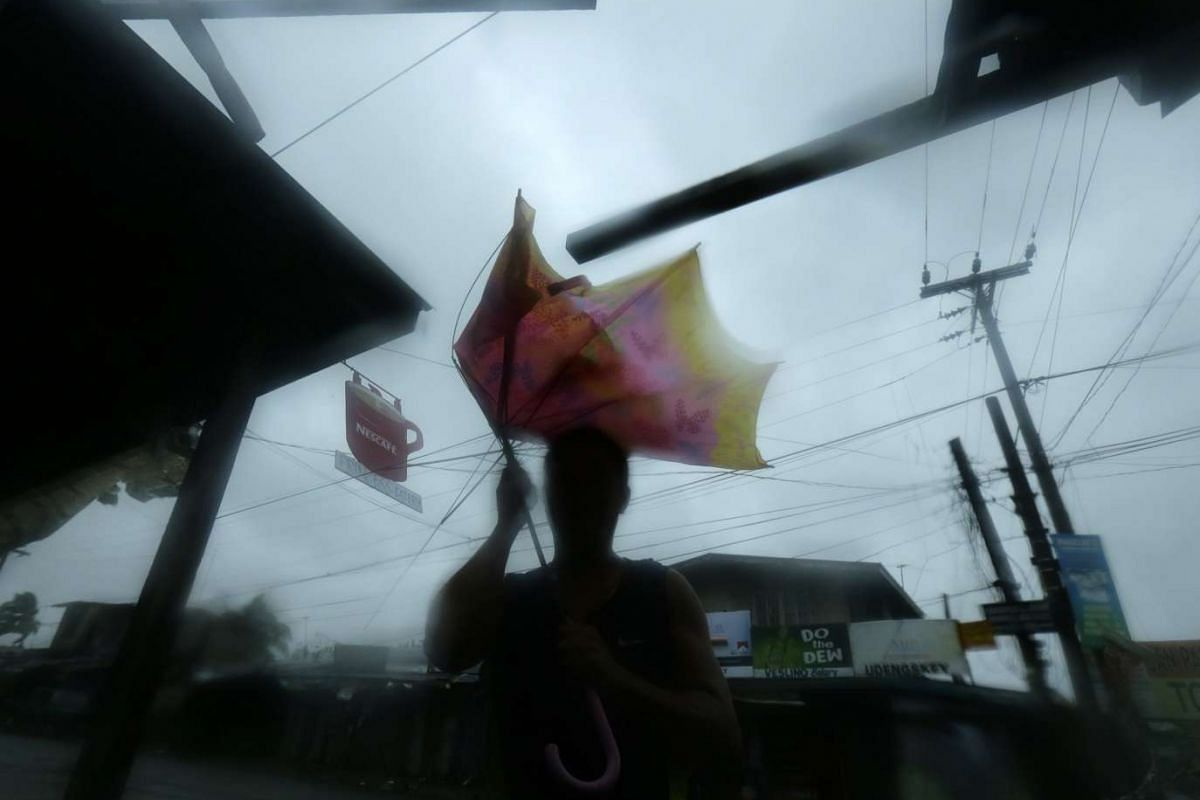 A man holding an umbrella blown by strong winds in the town of Munoz on Oct 18.