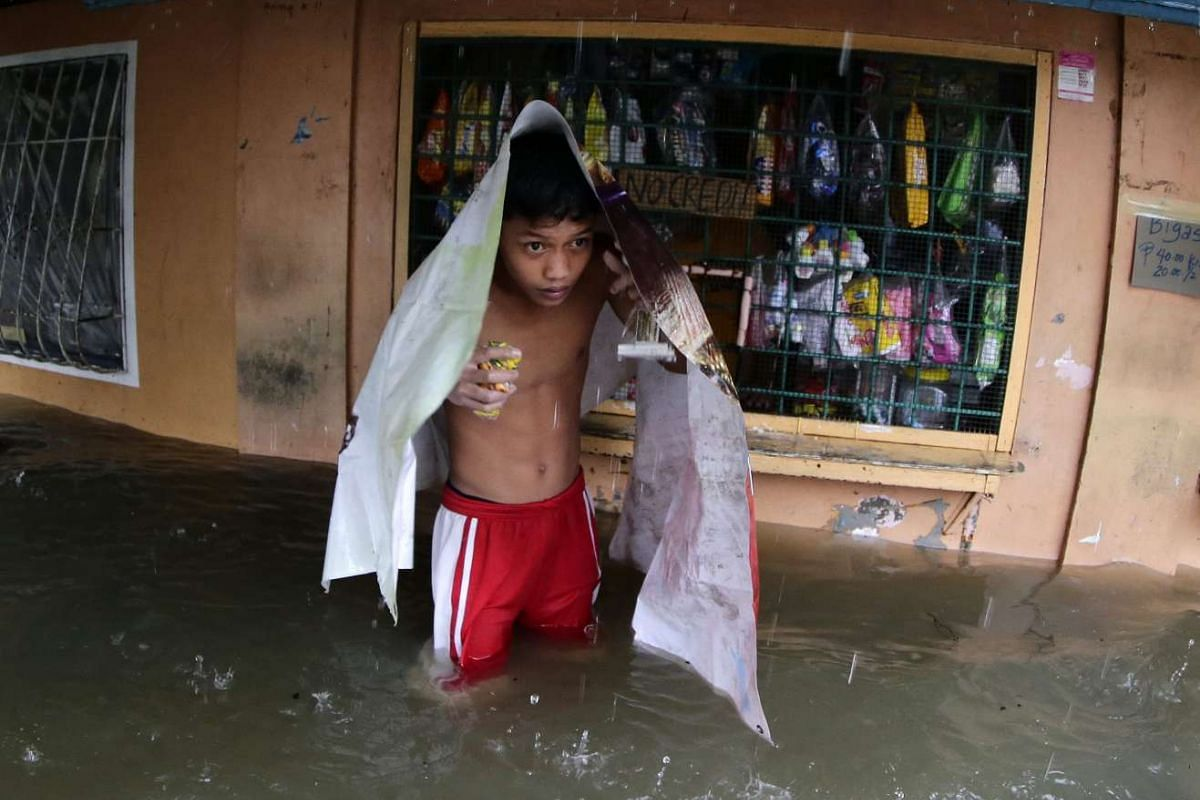 A boy buying snacks at a flooded store in San Jose city on Oct 18, 2015.