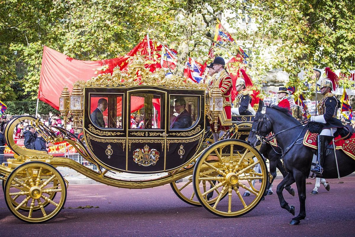 Britain's Queen Elizabeth II and China's President Xi Jinping travelling together in the Diamond Jubilee State Coach along the Mall to Buckingham Palace on Oct 20, 2015, as part of the ceremonial welcome for the Chinese President and his wife Peng Li
