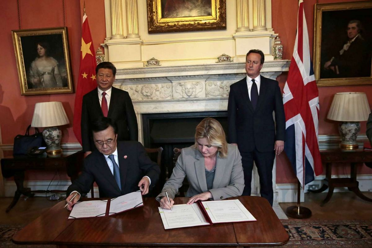 Britain's International Development Secretary Justine Greening (front, right) and China's Minister of Commerce Gao Hucheng signing an agreement as Britain's Prime Minister David Cameron (right) and Chinese President Xi Jinping watch at Number 10 Down