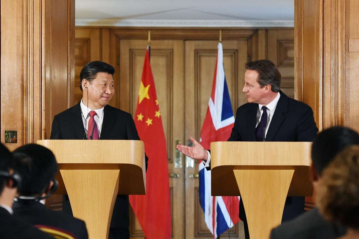 British Chancellor George Osborne (second, right) with an unidentified member of the Chinese delegation (left) during a signing ceremony on infrastructure with British Prime Minister David Cameron (right) and Chinese President Xi Jinping (second, lef