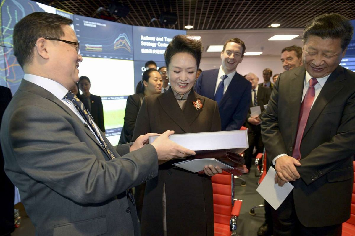 Chinese President Xi Jinping (right) reacting as his wife, Peng Liyuan, is presented with a gift by Professor Yike Guo during a visit to Imperial College in London on Oct 21, 2015.