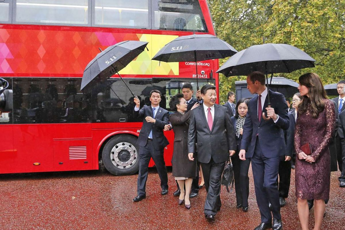Chinese President Xi Jinping (fourth, left) and his wife Peng Liyuan (second, left) walking with Britain's Catherine, Duchess of Cambridge (right), and Britain's Prince William, Duke of Cambridge (second, right), past a prototype of an Alexander Denn