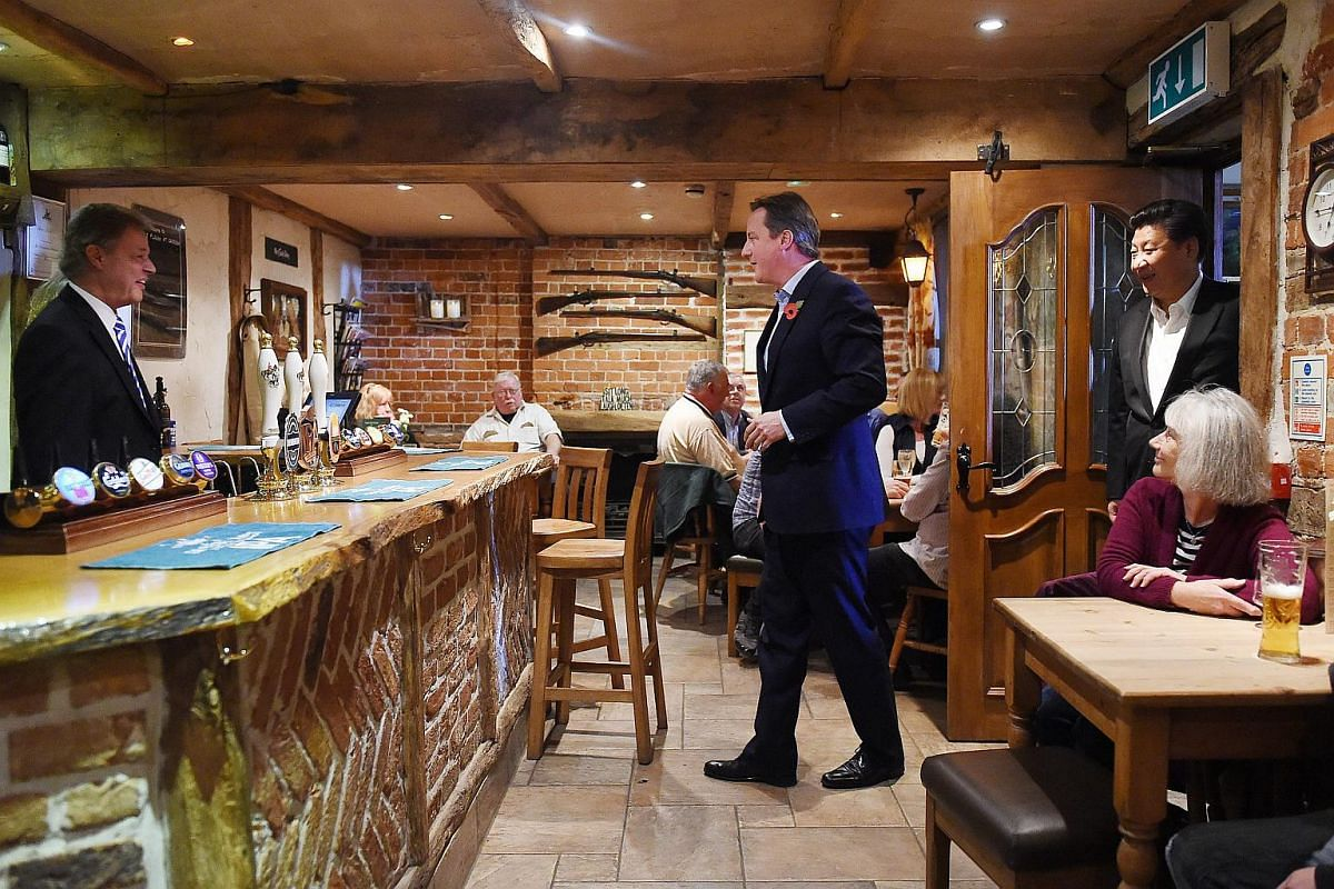 British Prime Minister David Cameron (centre) with Chinese President Xi Jinping (left) at a pub near Chequers, Buckinghamshire, north-west of London, Britain, on Oct 22, 2015.