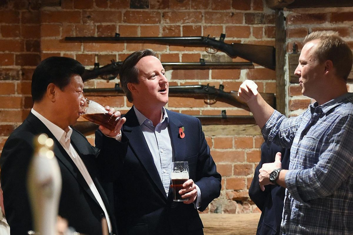 British Prime Minister David Cameron (centre) sharing a pint with Chinese President Xi Jinping (left) at a pub in Cadsden, Britain on Oct 22, 2015.