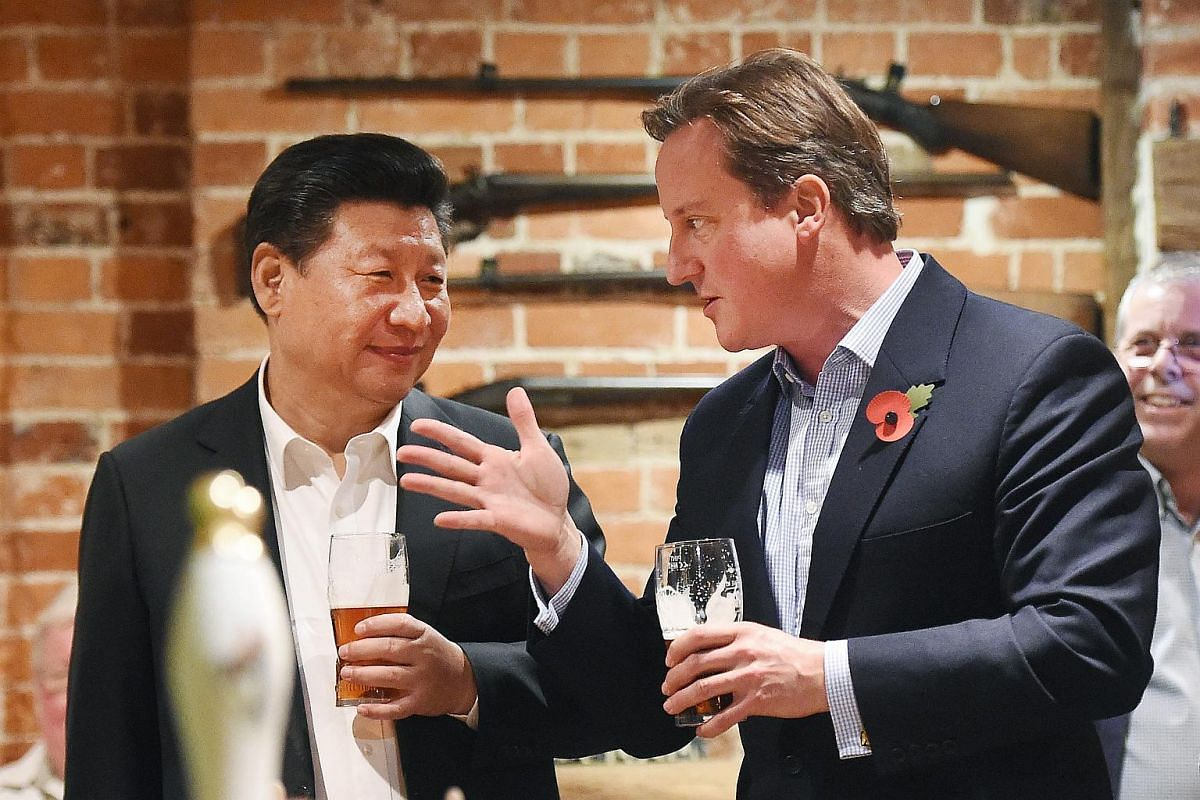 British Prime Minister David Cameron (right) sharing a pint with Chinese President Xi Jinping (left) at a pub in Cadsden, Britain on Oct 22, 2015.