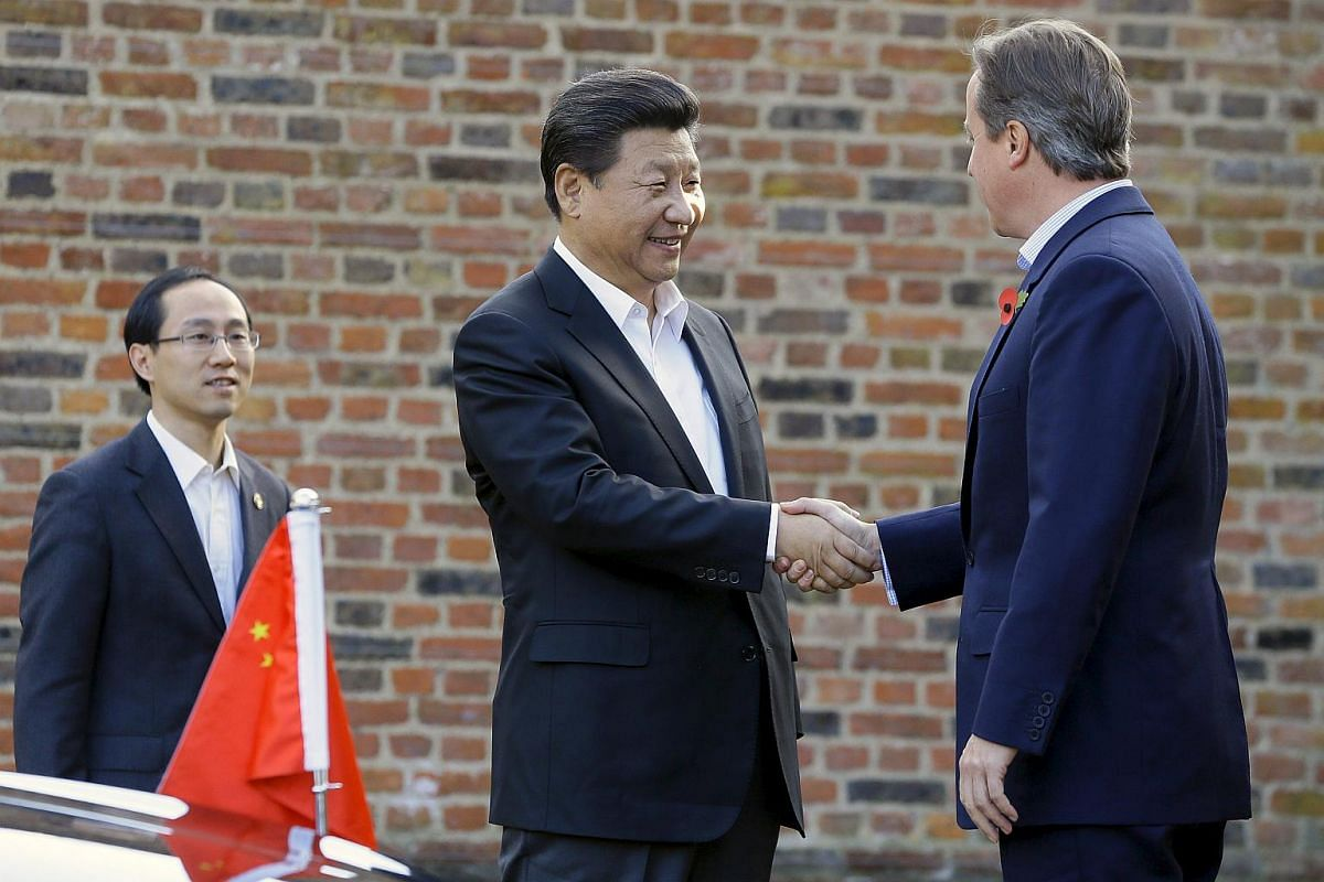 Britain's Prime Minister David Cameron (right) welcomes Chinese President Xi Jinping to his official residence at Chequers on Oct 22, 2015.