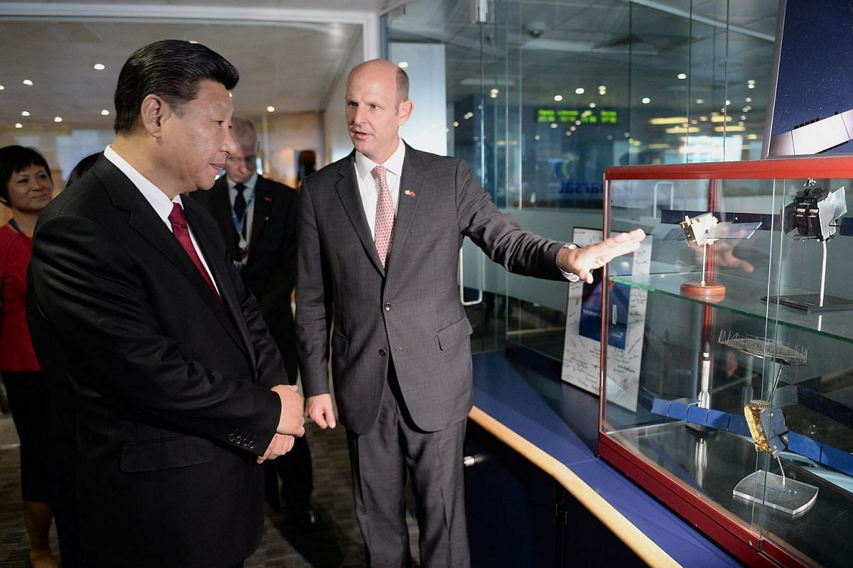 Chinese President Xi Jinping (left) views models of satellites with Rupert Pearce (right), CEO of Inmarsat, during a visit in London on Oct 22, 2015.