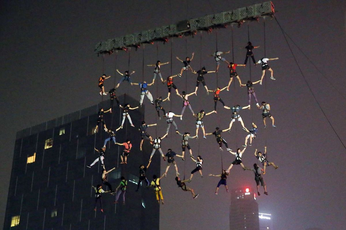 Forty-two volunteers are suspended over the Singapore River in a rehearsal for the Human Net act by Spanish performance troupe La Fura dels Baus. A 220-tonne crane will be used to suspend the human net over Clarke Quay.