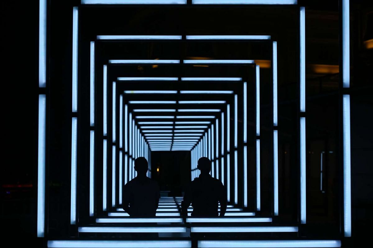 The silhouettes of artists Joel Rodiere (left) and Pierre Rodiere are seen in their creation named 160. It comprises 160 light bars covering an area of about 60m.