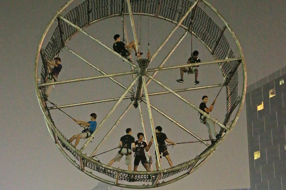 Eight parkour athletes climbing inside a wheel while suspended over the Singapore River as part of the rehearsal for the Singapore River Festival. This act is choreographed by Spanish troupe La Fura dels Baus.