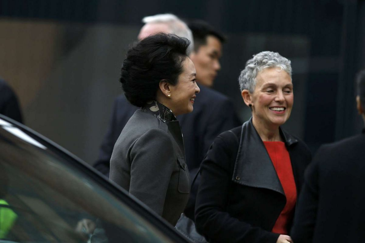 Peng Liyuan (left), wife of China's President Xi Jinping, arrives at the Museum of Science and Industry in Manchester on Oct 23, 2015.