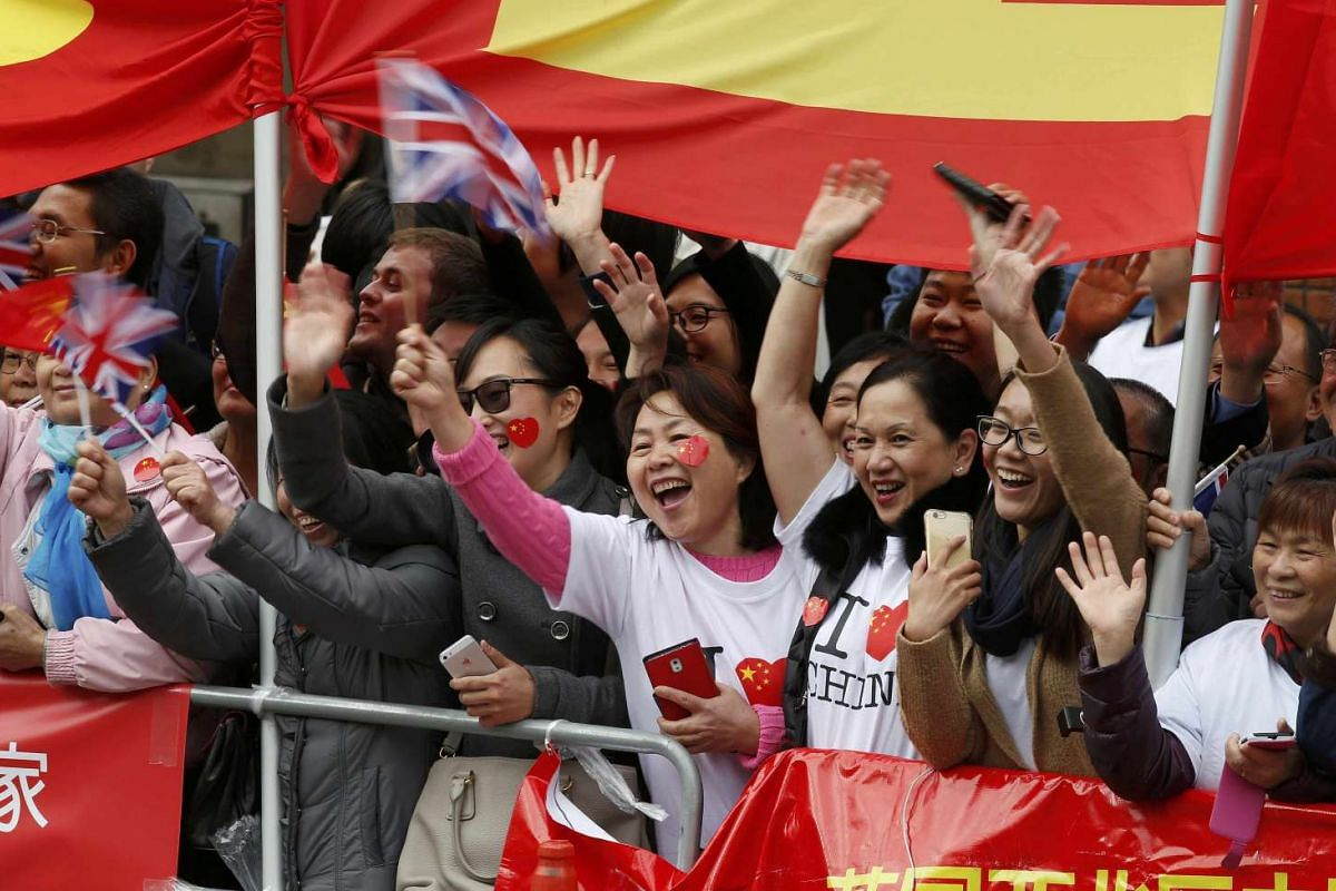 Supporters wave flags and cheer as they wait for the arrival of China's President Xi Jinping at Manchester Town Hall on Oct 23, 2015.